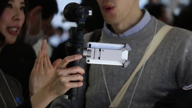 visitors try out dji osmo a camera stabilizer at sz dji technology cos booth of the cp camera and photo imaging show in yokohama kanagawa prefecture... - stabilisers stock videos & royalty-free footage
