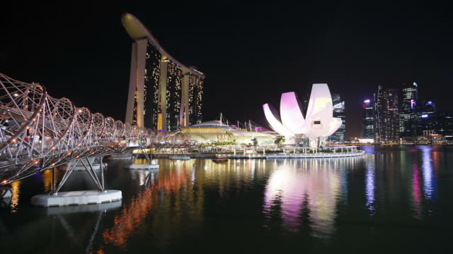 visitors use the illuminated helix bridge at the marina bay sands in singapore. - marina bay sands stock videos and b-roll footage