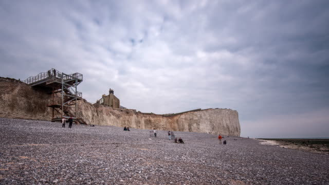 visitors use the steel staircase to access the pebble beach at birling gap the lowest point in the chalk cliffs of the seven sisters on the south coast of england - イングランド ケント点の映像素材/bロール