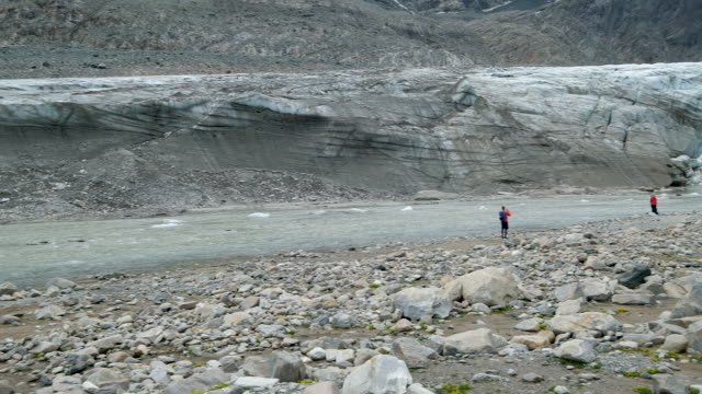 visitors walk along a river of meltwater flowing next to a sediment-covered-wall of ice of the retreating pasterze glacier on august 14, 2019 near... - human tongue stock videos & royalty-free footage