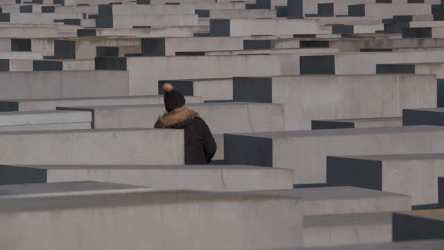 visitors walk among stellae at the memorial to the murdered jews of europe which commemorates jews murdered by the nazis in the holocaust on january... - holocaust stock videos & royalty-free footage