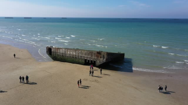 vídeos de stock, filmes e b-roll de visitors walk among the remains of the world war ii allied temporary mulberry harbor built during the dday invasion at the beach on april 30 2019 at... - arromanches