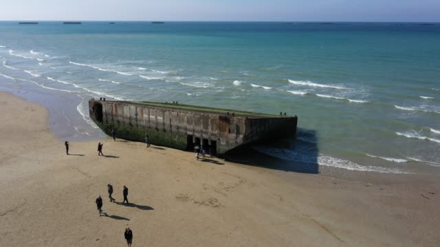 Visitors walk among the remains of the World War II Allied temporary Mulberry harbor built during the DDay invasion at the beach on April 30 2019 at...