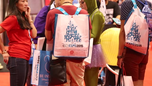 Visitors walk around inside the D23 Expo 2015 in Anaheim California US on Friday Aug 14 2015 Shots Visitors to the convention walk around wearing...