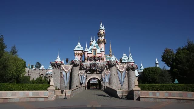 Visitors walk down the Main Strip of Disneyland in Anaheim California Visitors walk towards Sleeping Beauty Castle in Disneyland Disneyland Main St...