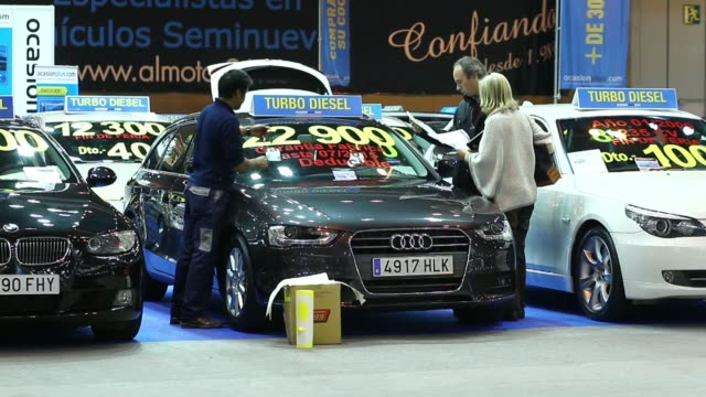 Visitors walk past Peugeot automobiles manufactured by PSA Peugeot Citroen standing on display during the secondhand vehicle show at the IFEMA Trade...