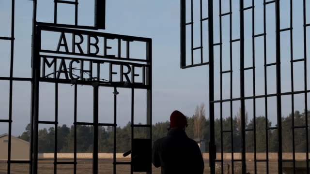 """visitors walk past the infamous entrance gate that reads: """"arbeit macht frei"""", or """"work sets one free"""" at the sachsenhausen concentration camp... - infamous stock videos & royalty-free footage"""