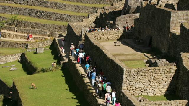 visitors walk past the royal palace at peru's machu picchu ruins. - マチュピチュ点の映像素材/bロール