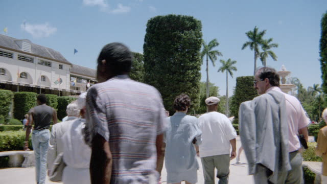 visitors walk through a courtyard near the horse races in miami, florida. - country club stock videos & royalty-free footage