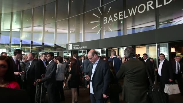 visitors walk through a display hall during the baselworld watch fair in basel visitors stand outside baselworld venue a visitor walks past a wall... - trade show booth stock videos & royalty-free footage