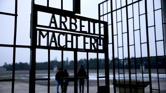 visitors walk through a gate past the inscription 'work sets you free' at the sachsenhausen concentration camp memorial on january 25, 2019 in... - international holocaust remembrance day stock videos & royalty-free footage
