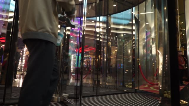 Visitors walk through revolving doors at the City of Dreams Manila casino resort operated by Melco Crown Philippines Resorts Corp a unit of Melco...