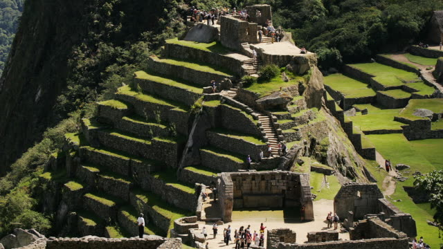 Visitors walk through the Sacred Plaza at Peru's Machu Picchu ruins.