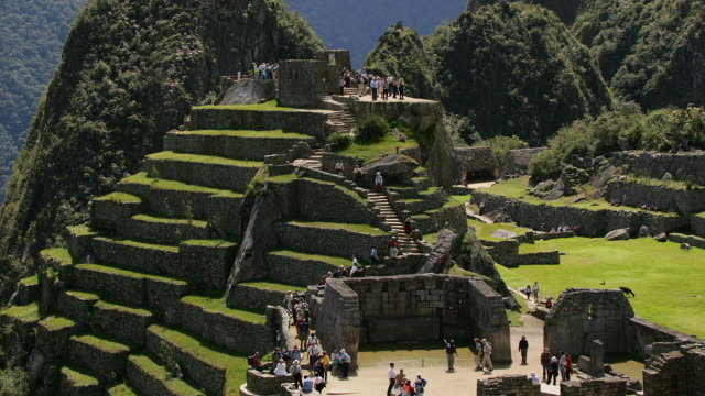 Visitors walk through the Sacred Plaza at Peru's Machu Picchu ruins.
