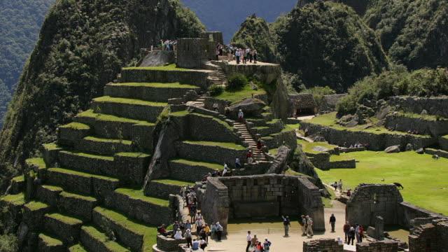 visitors walk through the sacred plaza at peru's machu picchu ruins. - machu picchu stock videos & royalty-free footage