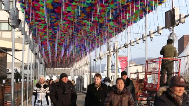 visitors walk toward the olympic stadium under a decoration as a laborer still works on them ahead of the 2018 pyeongchang winter olympic games in... - winter sports event stock videos and b-roll footage