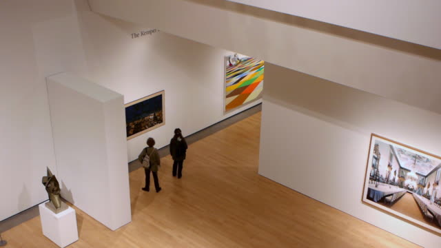 WS Visitors walking in art museum exhibiting modern paintings / Phoenix, Arizona, USA