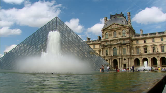 visitors walking past water fountain and pyramid at louvre / paris, france - louvre stock videos and b-roll footage