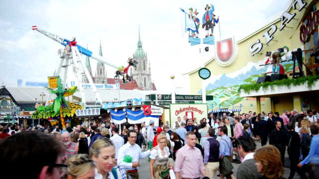 visitors walking through oktoberfest fairgrounds - fairground stall stock videos & royalty-free footage