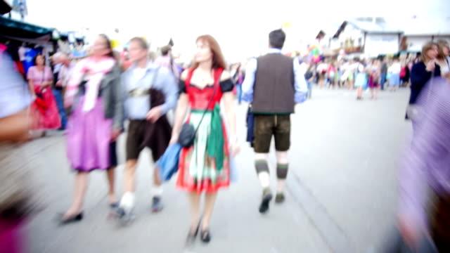 pov t/l visitors walking through oktoberfest fairgrounds - fairground stall stock videos & royalty-free footage