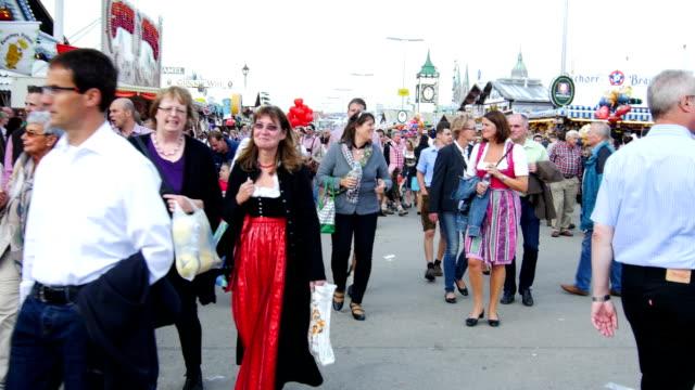 pov visitors walking through oktoberfest fairgrounds - fairground stall stock videos & royalty-free footage