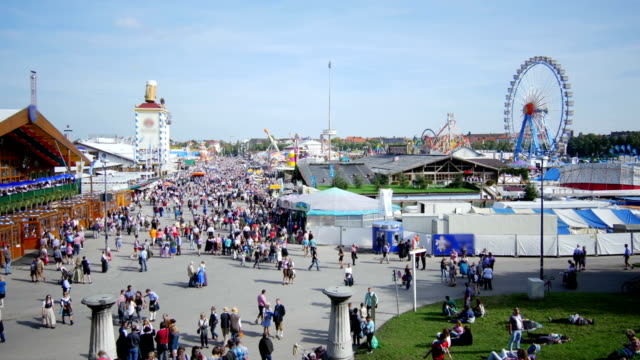 visitors walking through oktoberfest fairgrounds (4k/uhd to hd) - fairground stock videos and b-roll footage