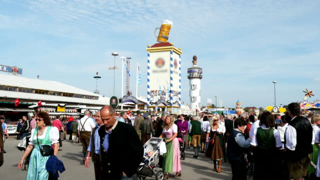 visitors walking through oktoberfest fairgrounds (4k/uhd to hd) - german culture stock videos and b-roll footage