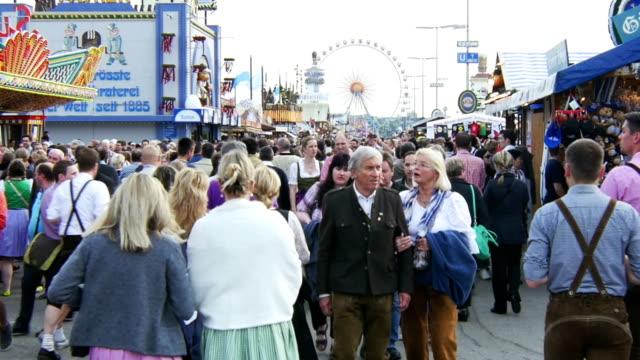 visitors walking through oktoberfest fairgrounds (4k/uhd to hd) - fairground stall stock videos & royalty-free footage