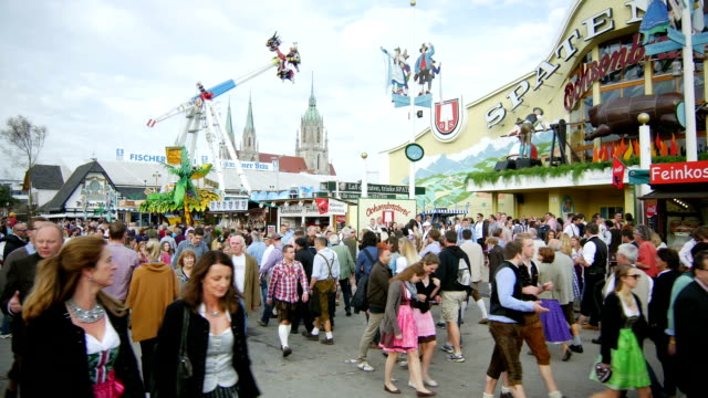 visitors walking through oktoberfest fairgrounds (4k/uhd to hd) - traditional clothing stock videos & royalty-free footage