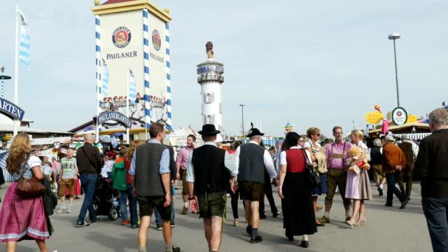 visitors walking through oktoberfest fairgrounds (4k/uhd to hd) - german culture stock videos & royalty-free footage