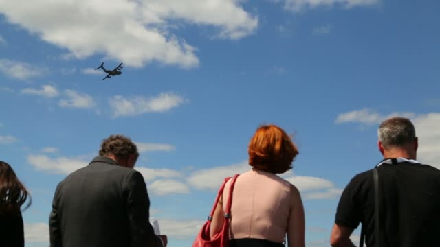 visitors watch as a airbus a350 wide body aircraft produced by airbus group nv performs in an aerial flying display on the first day of the... - airbus stock-videos und b-roll-filmmaterial
