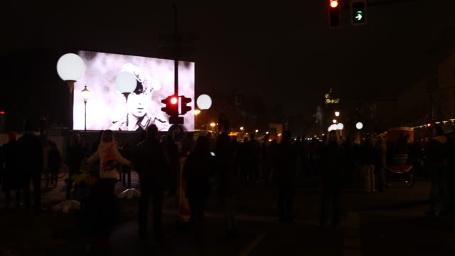 Visitors watching archive recordings of the GDR's wall security guard projected on big screen behind the light installation with balloons LICHTGRENZE...