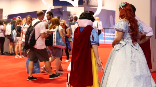 Visitors wearing Disney themed costumes walk around inside the D23 Expo 2015 in Anaheim California US on Friday Aug 14 2015 Shots Women walk around...