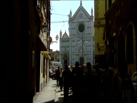 vídeos de stock e filmes b-roll de vista santa croce basilica of florence at end of tight alleyway filled with people silhouetted against the sun - 1995