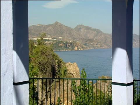 vista through white pillars and black railings looking onto almijara mountains in background and ocean in foreground - eskapismus stock-videos und b-roll-filmmaterial