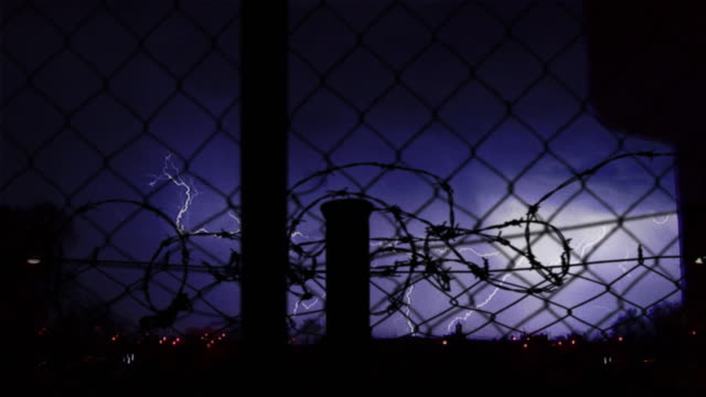 vídeos de stock, filmes e b-roll de visualization of intense lightning seen through a fence. - manipulação digital