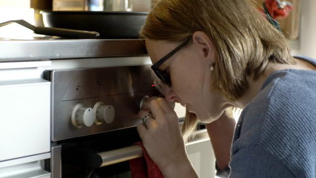 visually disabled woman using loupe while turning knob of gas stove burner in kitchen - blinds stock videos & royalty-free footage