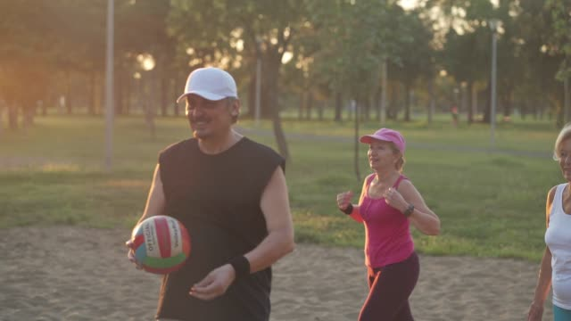 vital senior friends having fun while playing volleyball together in the sand at public park in sunset - sports period stock videos & royalty-free footage