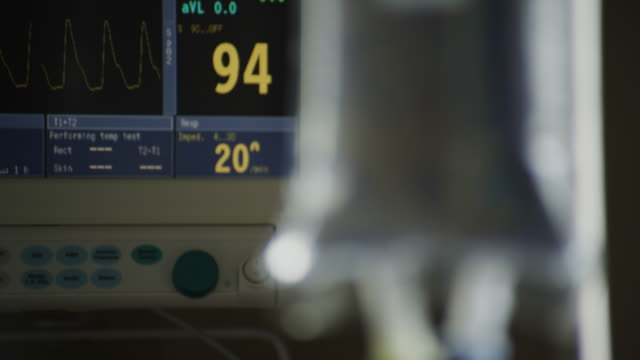 EKG vitals machine with LED readouts and a tight shot of a hanging IV bag.