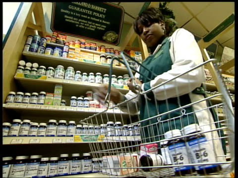 london int shop assistant in health food shop putting bottles of vitamin b6 tablets on shelves i/c - health food shop stock videos and b-roll footage