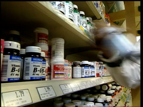 London Oxford St Holland Barrett INT Seq Shop assistant towards in health food shop and puts bottles of Vitamin B6 tablets on shelf McGinty i/c