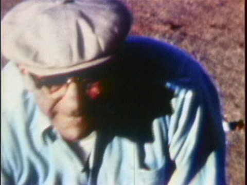 of vito genovese's face as he stands in a prison yard, bending over to pick something up and tossing it. he is wearing a grey cap, glasses, and a... - bending over stock videos & royalty-free footage