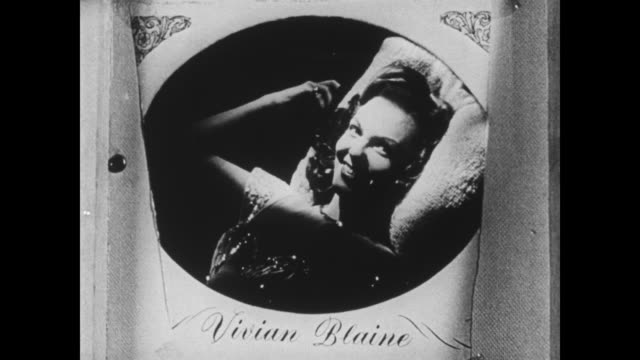 Vivian Blaine speaks from her photograph to a sailor