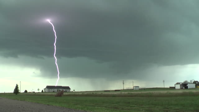 a vivid lightning bolt shoots out of a supercell thunderstorm and strikes the ground in rural nebraska - lightning strike stock videos and b-roll footage
