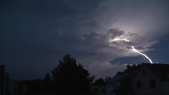 vídeos de stock, filmes e b-roll de a vivid lightning bolt streaks across the night sky as a severe thunderstorm approaches a residential neighborhood in nyc - bolt