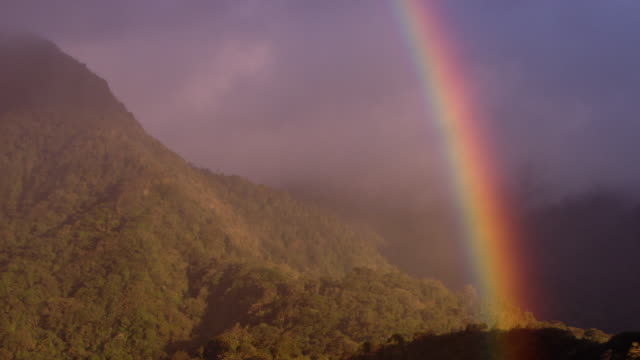 a vivid rainbow arcs across lush mountains. - rainbow stock videos & royalty-free footage