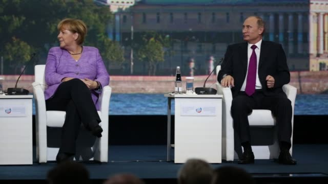 vladimir putin russia's president speaks during a session with angela merkel germany's chancellor on day two of the st petersburg international... - pult stock-videos und b-roll-filmmaterial