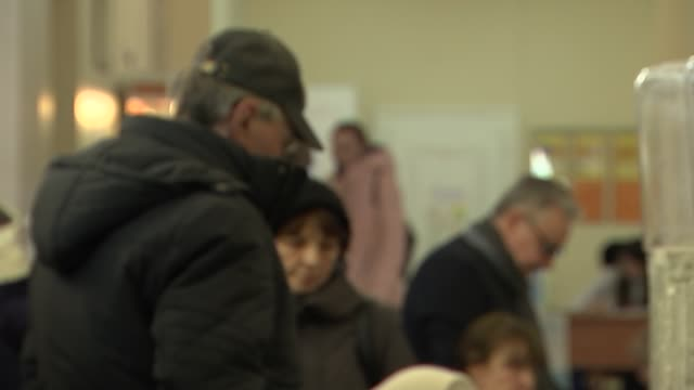 stockvideo's en b-roll-footage met vladimir putin wins presidential election gvs of polling day election badges and signage and voters about various of ksenia sobchak arriving at... - presidentsverkiezing