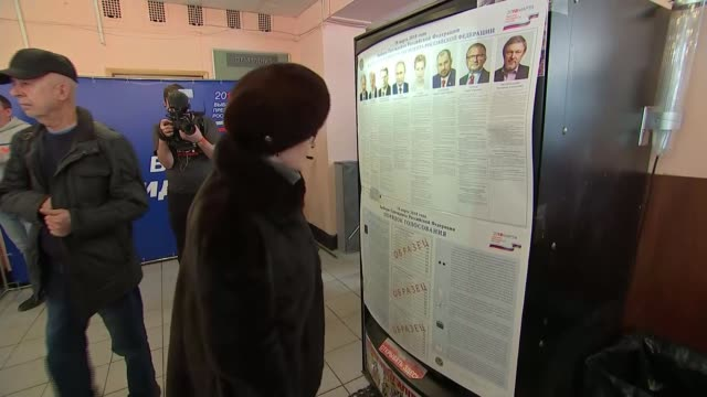 stockvideo's en b-roll-footage met vladimir putin wins presidential election moscow ext people arriving at polling station woman looking at poster showing russian presidential... - presidentsverkiezing