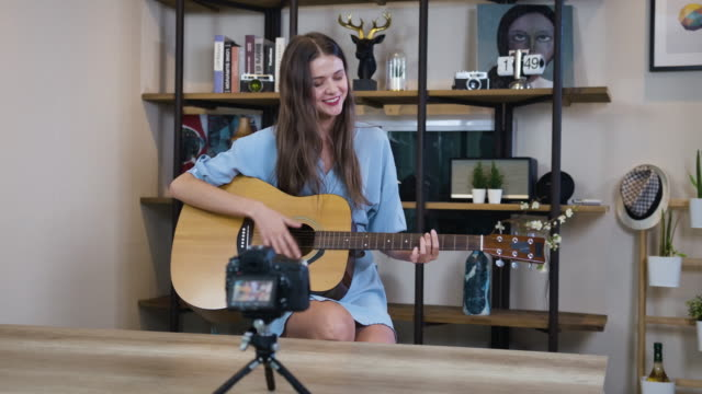 vlogger beautiful woman guitarist filming vlogg in living room - side hustle stock videos & royalty-free footage